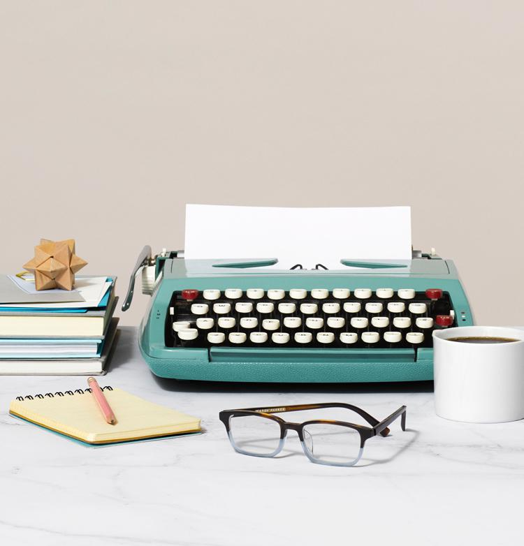 glasses, typewriter, notepad, books, and coffee mug on a table